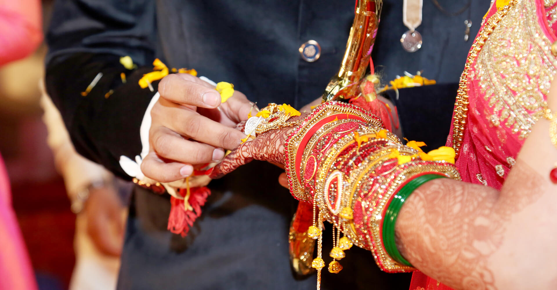 close-up of hands of indian groom placing wedding ring on his bride at an indian wedding
